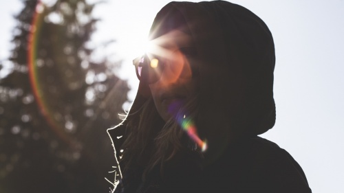 A girl wearing a jacket and hood looking at the camera with sunrays behind in head.