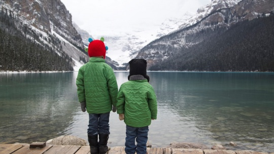 Two young boys look out over the water surrounded by mountains.