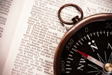 Compass laying on top of a Bible opened to Exodus 20 - where the 10 Commandments are listed.