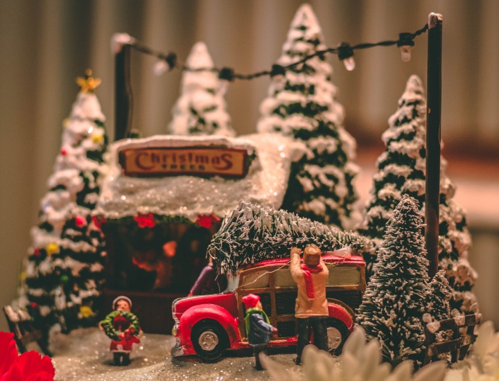 a miniature christmas scene of gathering a christmas tree