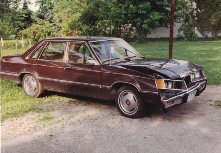Brown car with dented front hood