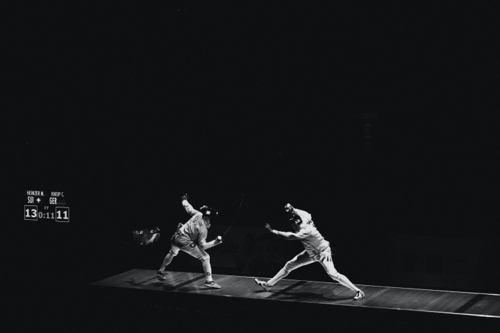 Two fencing partners sparring against a black background