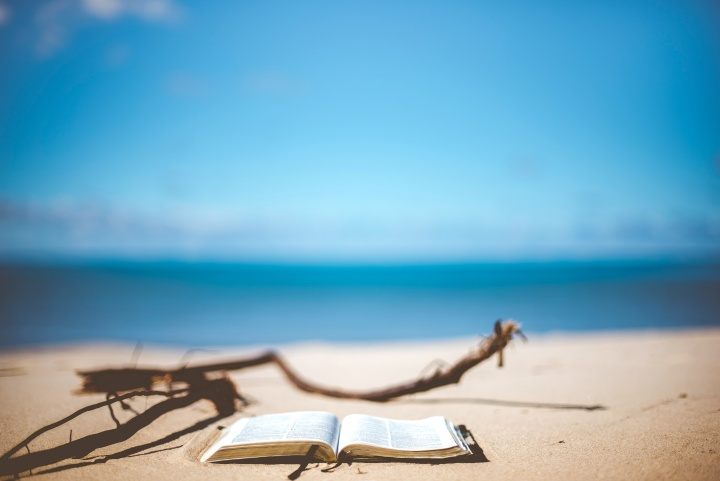 Bible resting on a beach overlooking the sea
