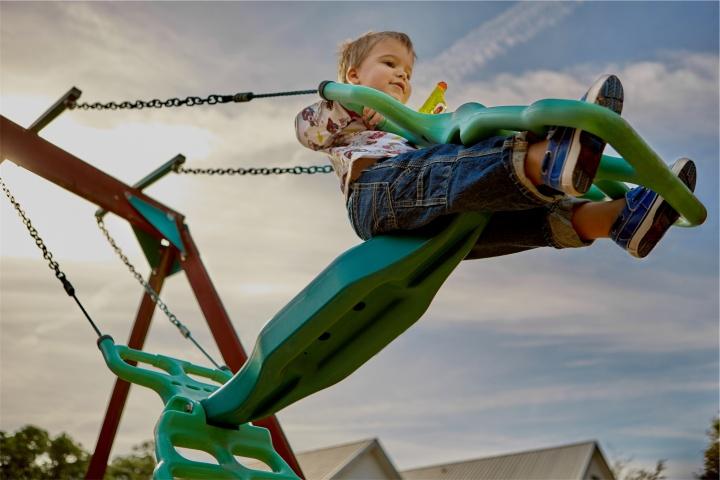 A little boy swinging on a swingset.