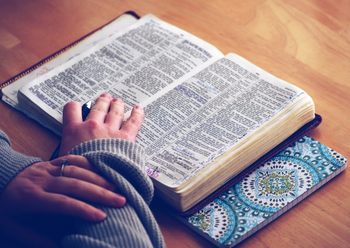 A woman with an open Bible laying on a table.