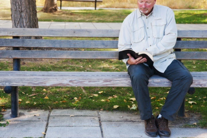 A man reading a Bible sitting on a park bench.