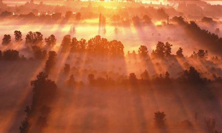 A foggy sunrise over farmlands.