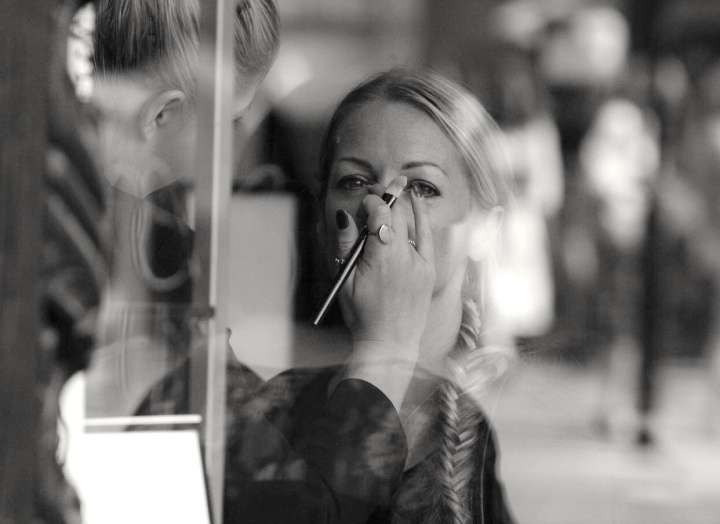 A woman getting makeup put on her in a salon.