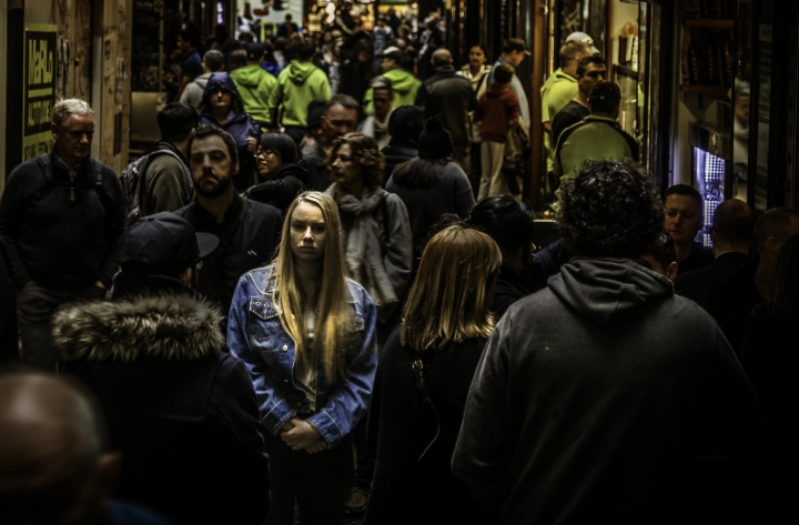 A woman walking in a crowded alley with numerous people.