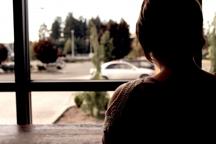 A woman looking out a window.