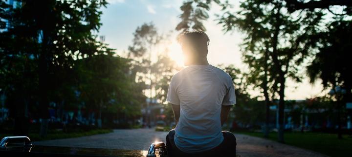 A teenage boy sitting by himself.