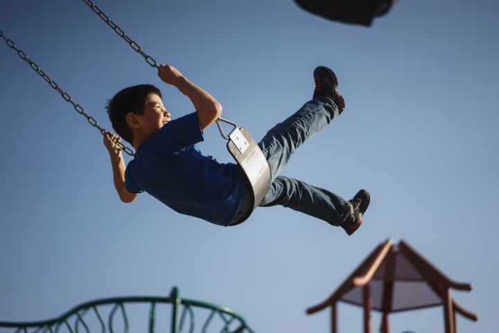 A boy swinging on a playground swing.