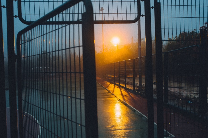A metal fence with its gate opening. The sun is rising in the background.