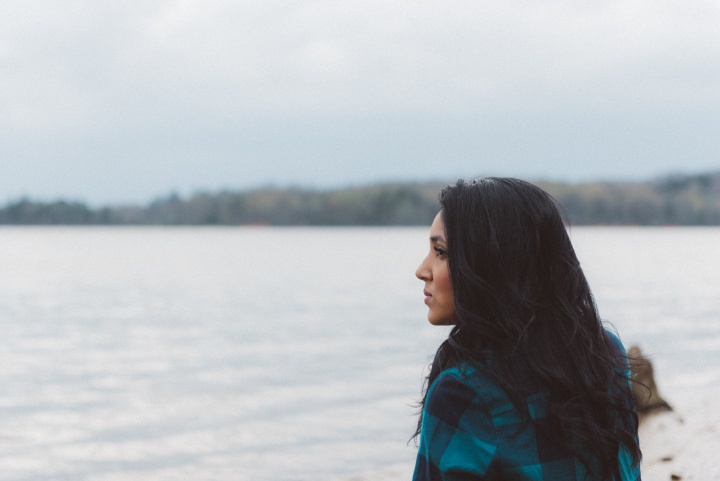 A woman looking out over a lake.