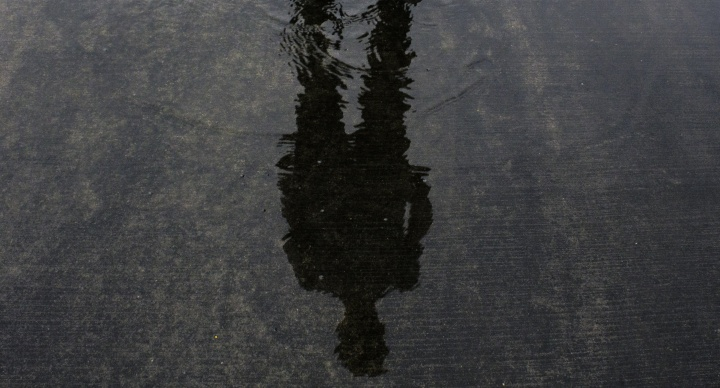 A person's shadow in shallow pool of water.