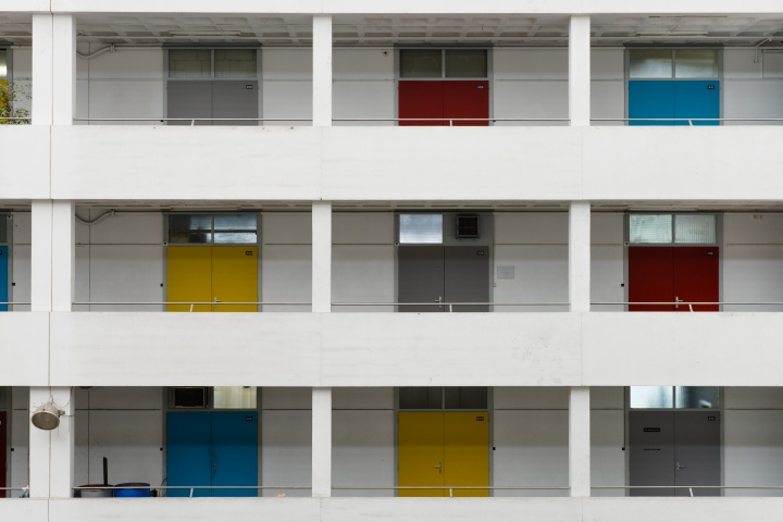 Outside of building with several floors featuring different colored doors.