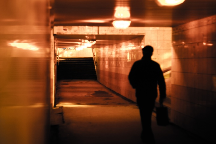 A man walking down a tunnel hallway.