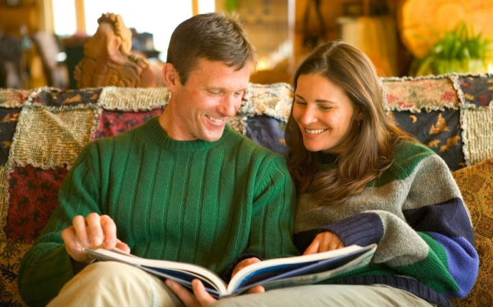A couple sitting together on a couch looking at a large book.