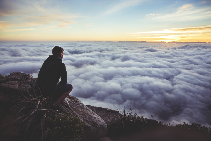 A man sitting on a rock looking out over the clouds covering a valley.
