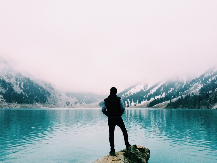A man staring a clear blue lake.