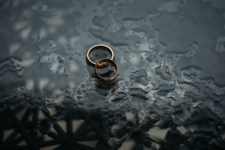 Two wedding rings lying a table.