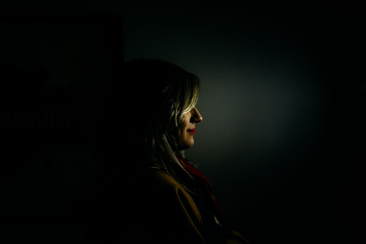 A woman standing in the dark.