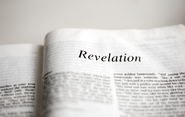 A Bible opened to first page of Revelation.
