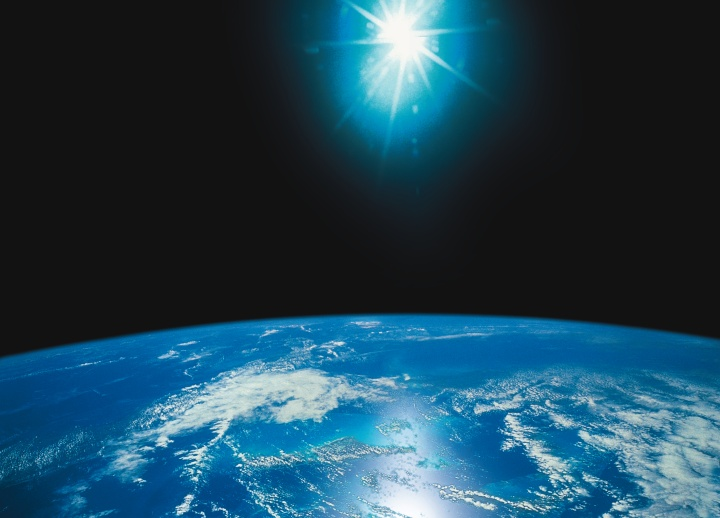 Photo illustration of bright light above the earth.