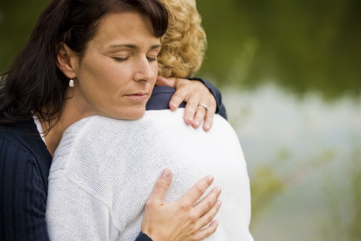 A woman hugging a grieving woman.