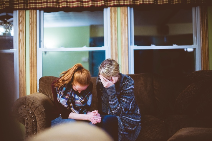 Two women sitting together on a couch crying.
