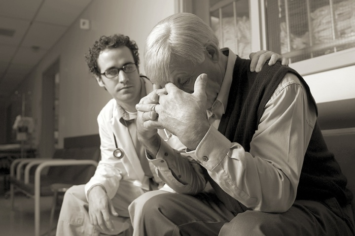 A doctor consoling a person who is grieving.