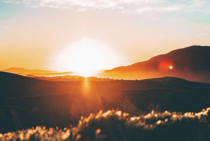 Sun rays shining over hills.