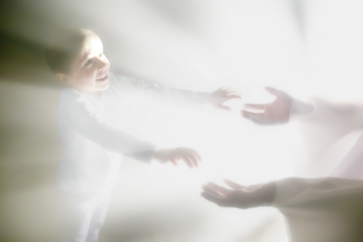 A photo illustration showing a person reaching for another person surrounded by bright lights.