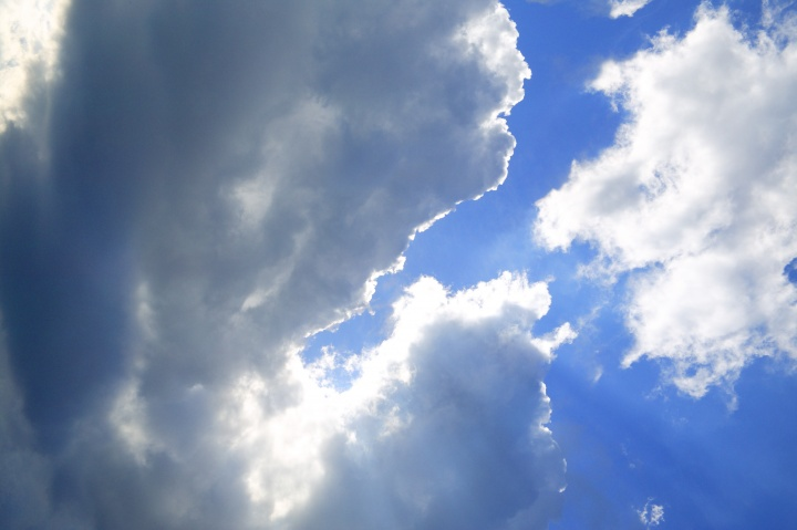 A blue sky with clouds and sun rays.