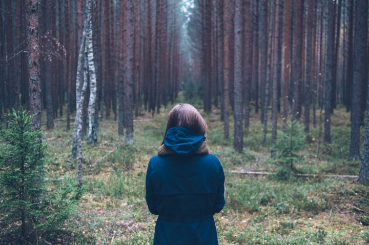 A young woman looking into a forest.