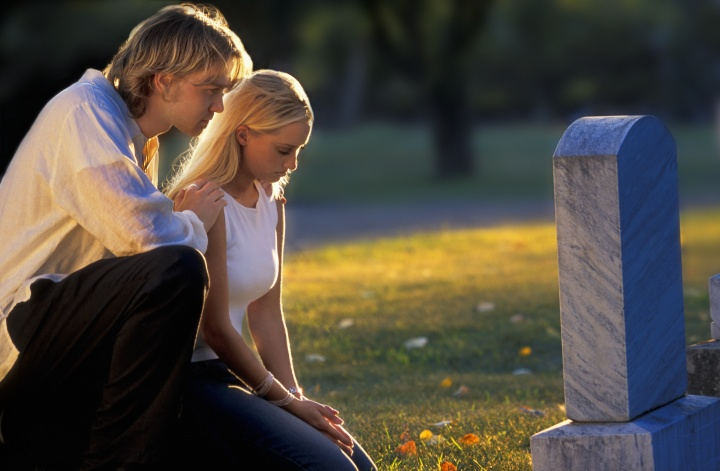 A young couple by a grave stone.