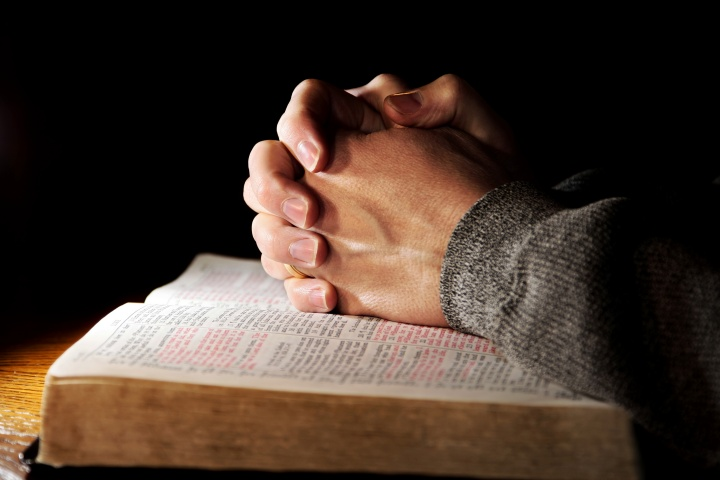 A man's hands clasped on top of a Bible.
