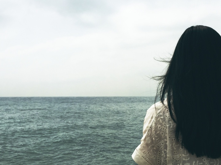 A woman looking out over a body of water.