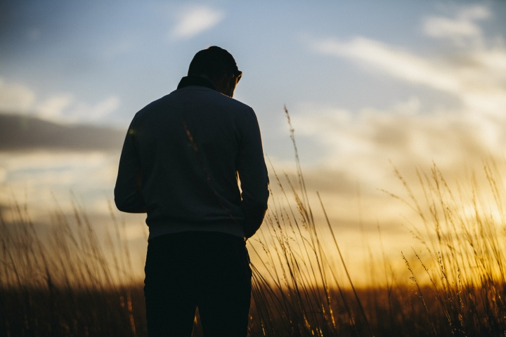 A silhouette of young man with the sun setting in the background.