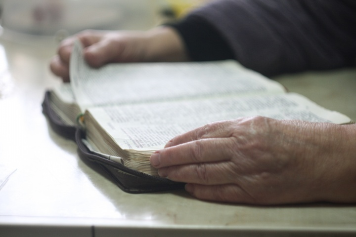 An old person's hands hold the edges of a Bible.