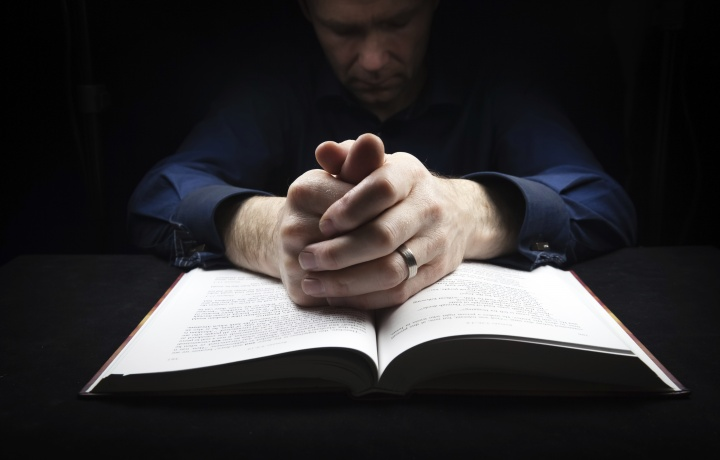 A man praying over his Bible.