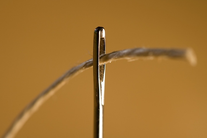 A thread going through the eye of a needle.