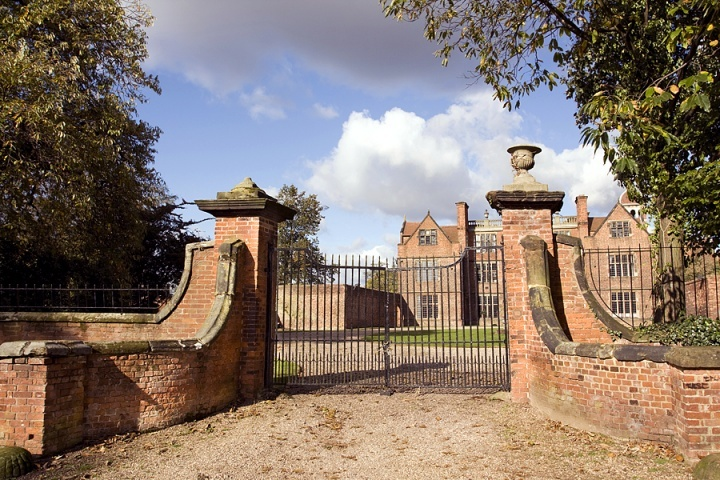 A big gate surrounding a large brick house.