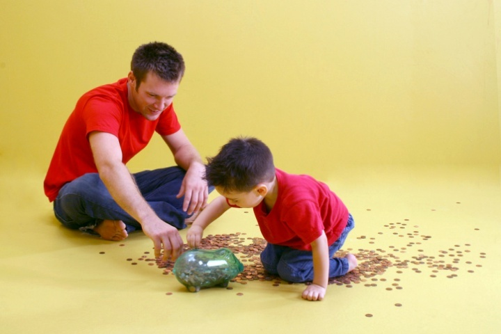 A father and son counting pennies from a glass jar.