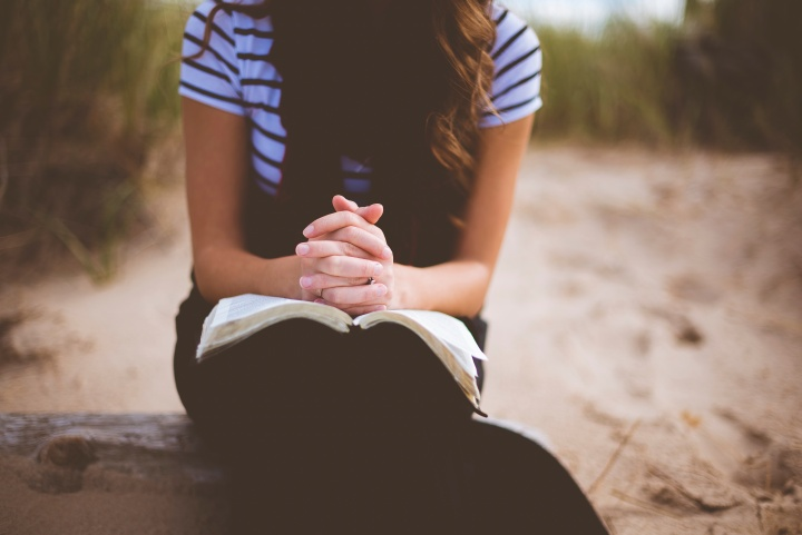 A woman with an open Bible on her lap.
