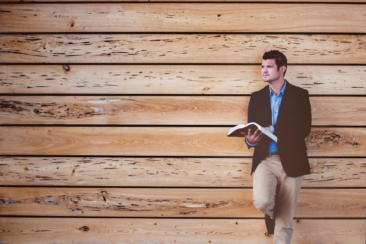 A man standing with a Bible with his back against a wall.