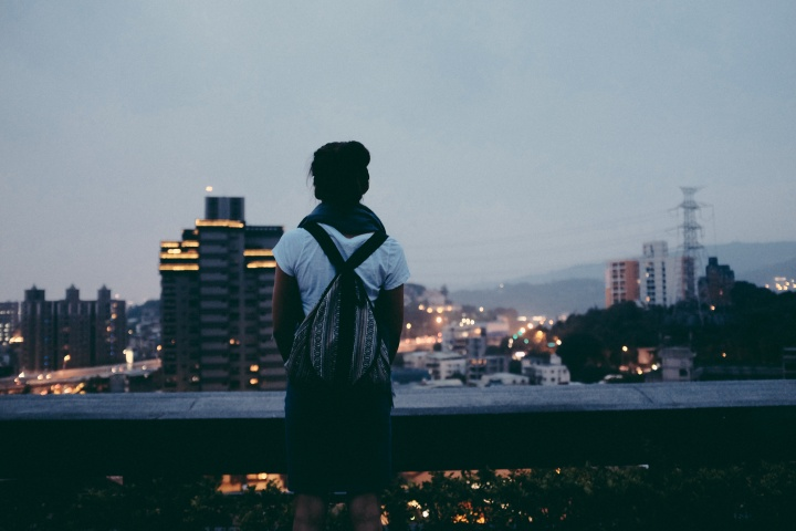 A young woman looking over a crowded city.