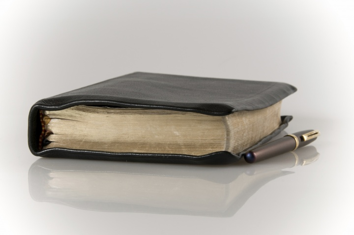 A Bible and pen laying on a table.