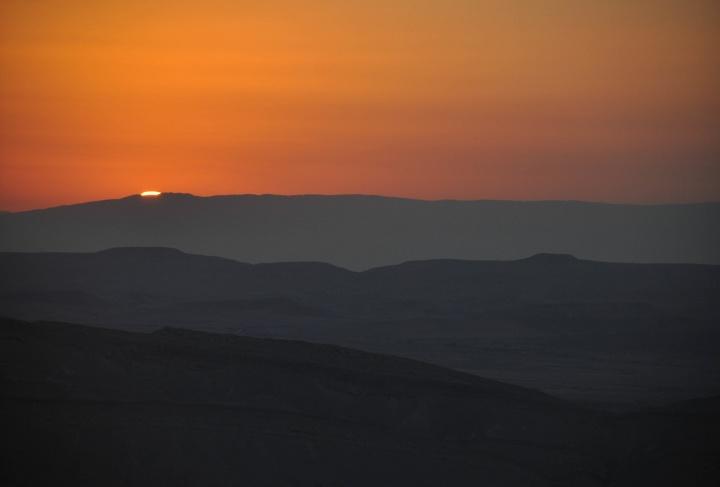 Sunset over desert hills.