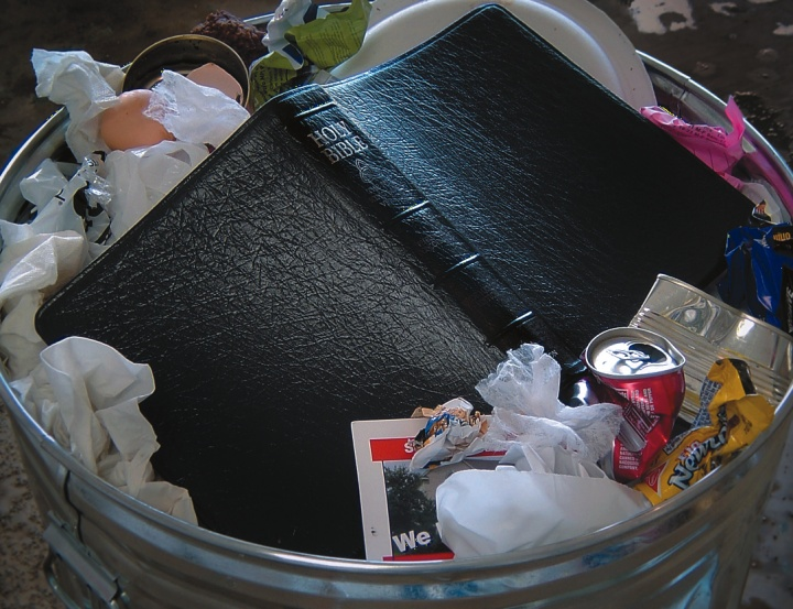 A Bible lying on garbage in a trash can.